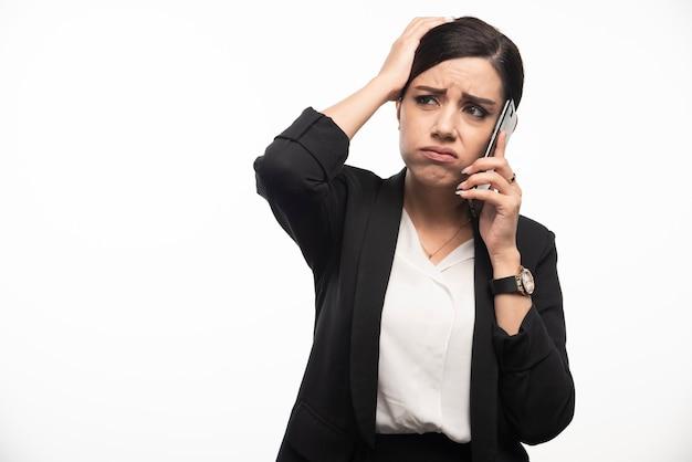 Portret van zakenvrouw praten over de telefoon op witte muur.