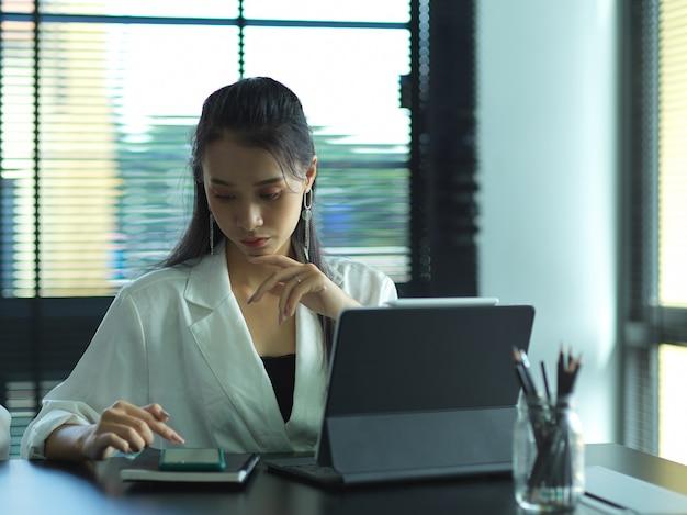 Portret van zakenvrouw werken met smartphone en digitale tablet op werktafel in kantoorruimte