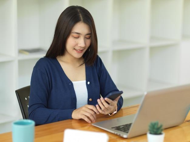 Portret van zakenvrouw werken met smartphone en laptop op werktafel in kantoorruimte