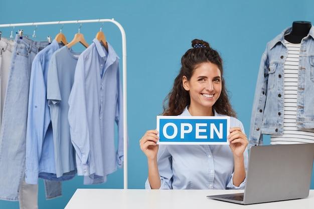 Portret van zakenvrouw zitten aan de tafel voor laptop met plakkaat open en glimlachend werkt ze in kledingwinkel