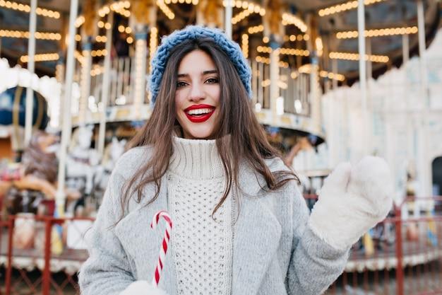 Portret van zalige langharige vrouwelijk model in witte handschoenen met riet van het suikergoed in pretpark. mooi meisje in blauwe hoed kerst vieren en poseren in de buurt van carrousel.