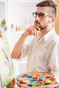 Portret van zeer begaafde schilder houdt borstel.