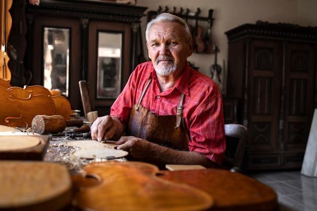 Portret van zeer ervaren senior vakman in zijn timmerwerkplaats met gereedschappen die aan zijn projecten werken
