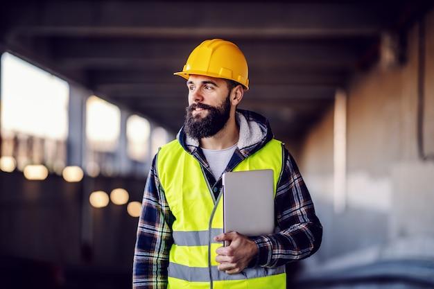 Portret van zeer gemotiveerde kaukasische hardwerkende lachende bebaarde supervisor met helm op hoofd in vest en met laptop in handen die zich voordeed op de bouwplaats.