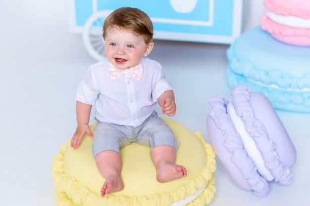 Portret van zeer mooie kleine jongenszitting op grote makaron en het glimlachen.