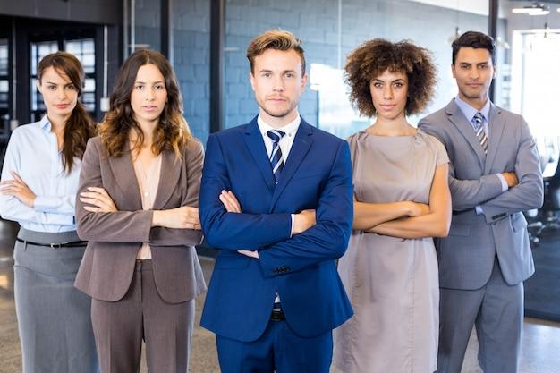 Portret van zeker commercieel team die zich in bureau met hun gekruiste handen bevinden