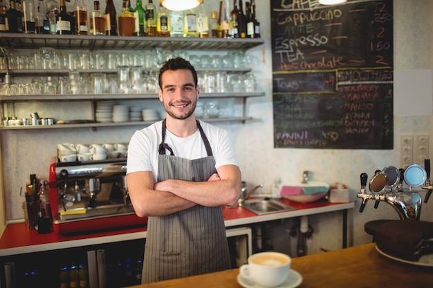 Portret van zekere barista met wapens die bij koffiehuis worden gekruist