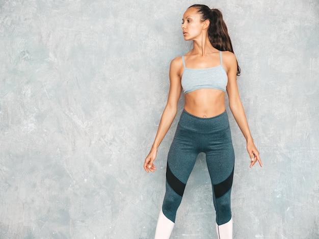 Portret van zekere fitness vrouw in sporten kleding die zeker kijken het vrouwelijke stellen in studio dichtbij grijze muur