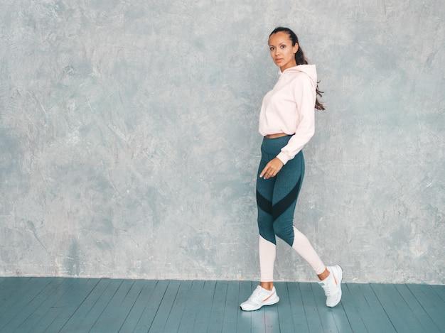 Portret van zekere fitness vrouw in sporten kleding die zeker kijken. vrouw die in studio dichtbij grijze muur lopen