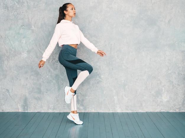 Portret van zekere fitness vrouw in sporten kleding die zeker kijken. vrouwelijk springen in studio dichtbij grijze muur