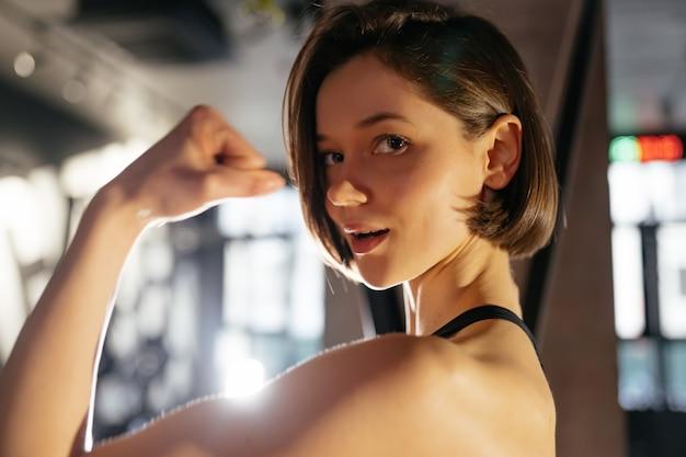 Portret van zekere gezonde donkerbruine vrouw die biceps toont