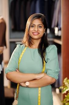 Portret van zekere jonge indische vrouwelijke ondernemer die zich in atelier bevindt dat zij bezit