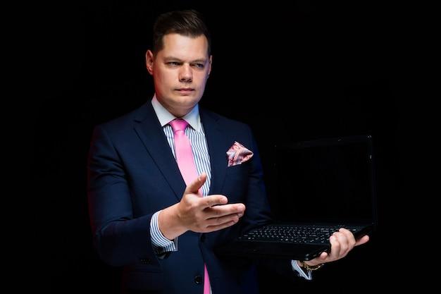 Portret van zekere knappe ernstige zakenman die op laptop tonen die handgebaar maken dat op zwarte wordt geïsoleerd
