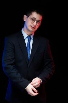 Portret van zekere knappe modieuze zakenman met hand op zijn kostuum op zwarte achtergrond