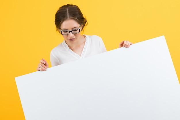 Portret van zekere mooie gelukkige glimlachende jonge bedrijfsvrouw die leeg aanplakbord op gele achtergrond tonen