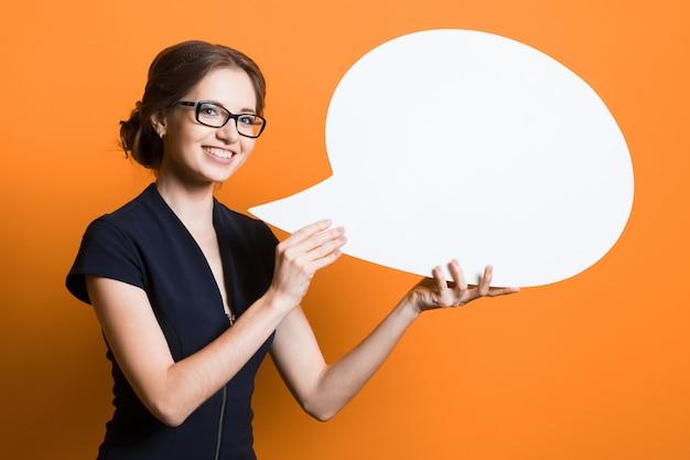 Portret van zekere mooie jonge bedrijfsvrouw met toespraakbel in haar handen die zich op oranje muur bevinden