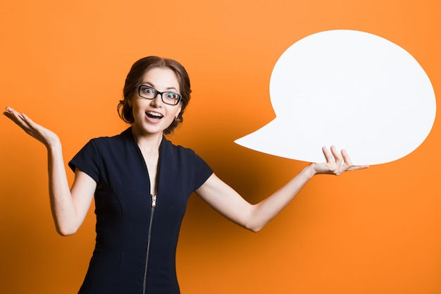 Portret van zekere opgewekte mooie jonge bedrijfsvrouw met toespraakbel in haar handen die zich op oranje achtergrond bevinden