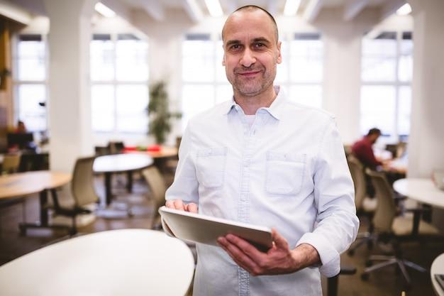 Portret van zekere zakenman met digitale tablet op creatief kantoor