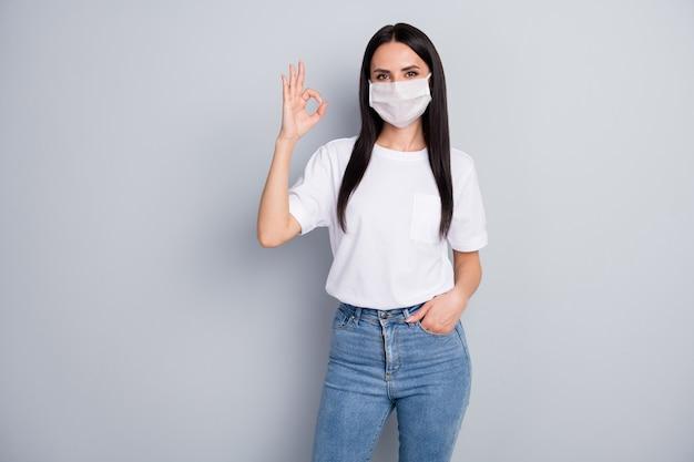 Portret van zelfverzekerd cool meisje geniet van corona virus veiligheid bescherming ademhalingsmasker kwaliteit goedkeuren toon ok teken dragen witte t-shirt denim geïsoleerd over grijze kleur achtergrond