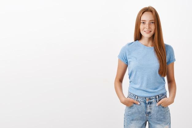 Portret van zelfverzekerd knap gember meisje met schattige sproeten in blauw t-shirt en spijkerbroek hand in hand in de zakken en lachend met zelfverzekerde uitdrukking