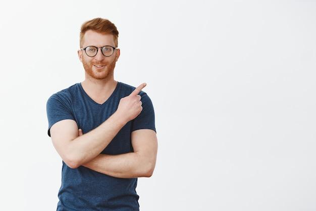 Portret van zelfverzekerd mannelijk en slim roodharig mannetje met varkenshaar in glazen, wijzend op de rechterbovenhoek