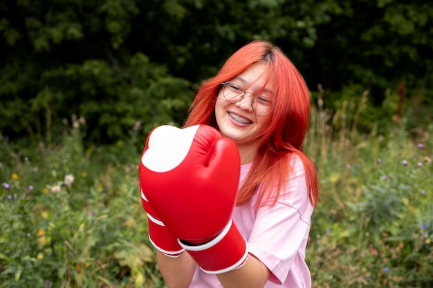 Portret van zelfverzekerd roodharig meisje met bokshandschoenen