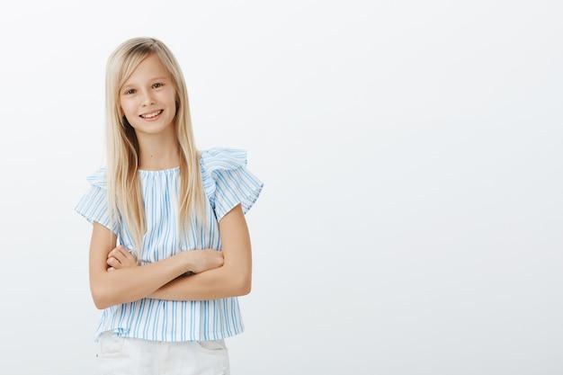 Portret van zelfverzekerd schattig europees meisje in blauwe blouse, hand in hand op borst gekruist en glimlachend met zelfverzekerde uitdrukking, energiek en vrolijk