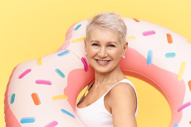 Portret van zelfverzekerde aantrekkelijke europese vrouw met pixie stijlvol kapsel poseren tegen gele achtergrond, uitvoering roze opblaasbare zwemmen cirkel, warme zonnige dag door zee of zwembad, glimlachend
