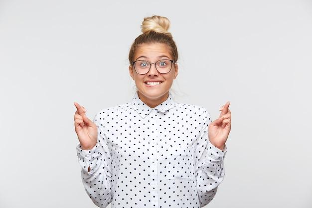 Portret van zelfverzekerde aantrekkelijke jonge vrouw met broodje draagt polka dot shirt en bril