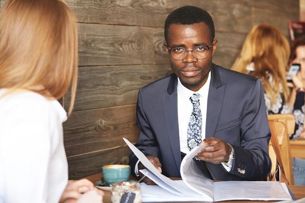 Portret van zelfverzekerde afrikaanse zakenman die in glazen met ernstige uitdrukking kijkt