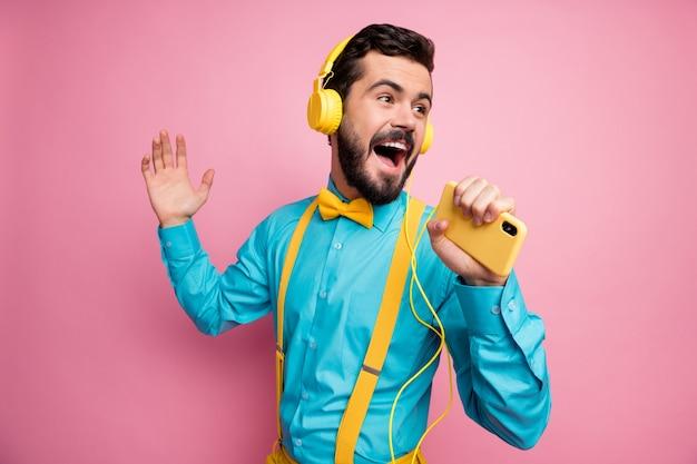 Portret van zelfverzekerde bebaarde man houdt telefoon zoals microfoon luisteren muziek koptelefoon