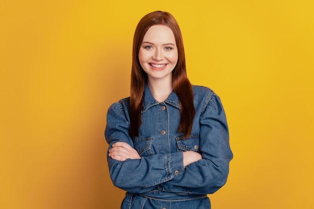 Portret van zelfverzekerde charmante dame gevouwen armen glanzende glimlach op gele achtergrond