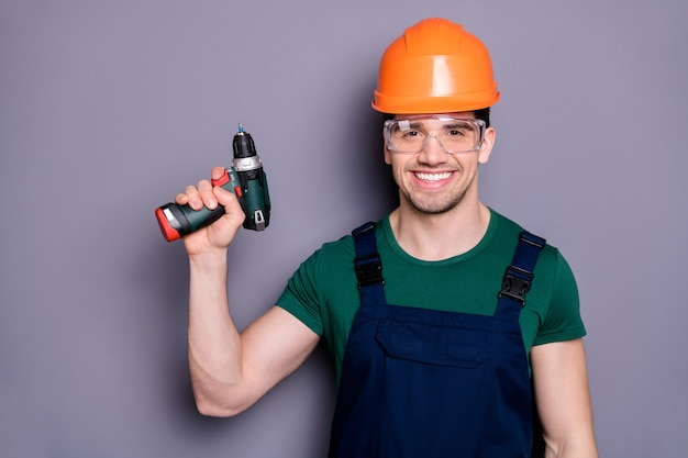 Portret van zelfverzekerde coole man reparateur houdt perforator klaar om plat appartement te vernieuwen draag blauwe overall groen t-shirt geïsoleerd over grijze kleur muur