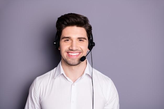 Portret van zelfverzekerde coole positieve callcentermedewerker kan helpen bij problemen, zwarte oortelefoons dragen, formele kleding dragen die over grijze kleurmuur wordt geïsoleerd