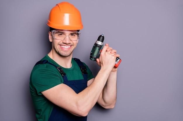Portret van zelfverzekerde coole reparateur klusjesman houden perforator klaar om appartement te repareren dragen oranje harde pet bril groen oranje t-shirt goed kijken geïsoleerd over grijze kleur muur