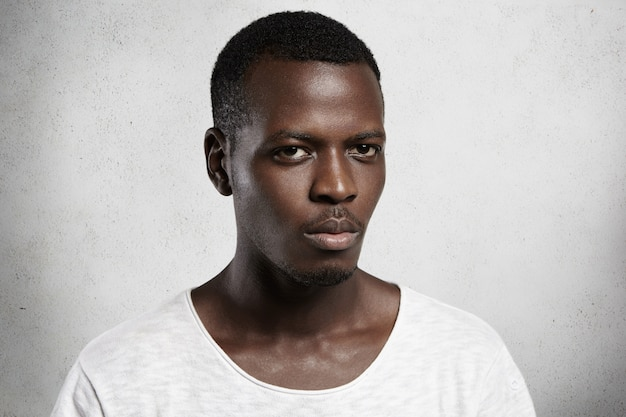 Portret van zelfverzekerde en knappe jonge afrikaanse man terloops gekleed met ernstige of boze gezichtsuitdrukking.