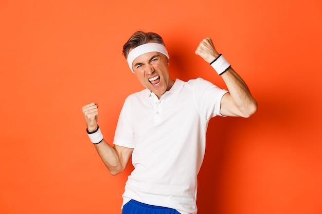 Portret van zelfverzekerde en vrolijke man van middelbare leeftijd in sportkleding