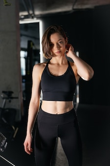Portret van zelfverzekerde gezonde donkerbruine vrouw, gekleed in sportkleding staande sportschool