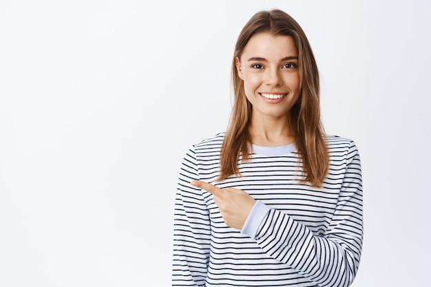 Portret van zelfverzekerde glimlachende vrouw met blond haar, wijzende vinger naar links naar logobanner en starend naar voren, advertenties tonend op witte muur, casual gestreept shirt dragen