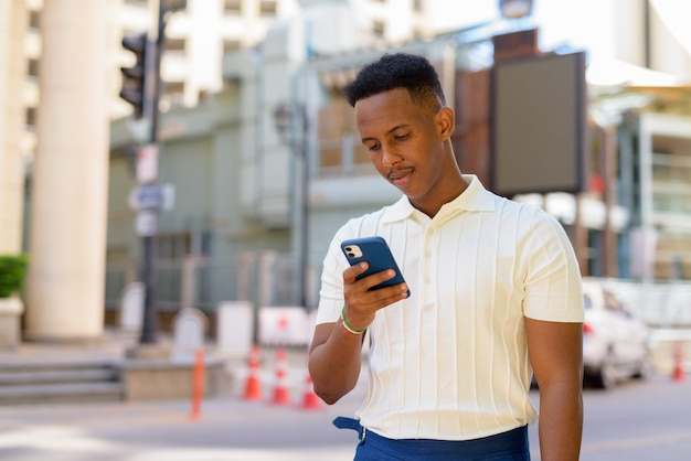 Portret van zelfverzekerde jonge afrikaanse zakenman die vrijetijdskleding draagt en mobiele telefoon gebruikt