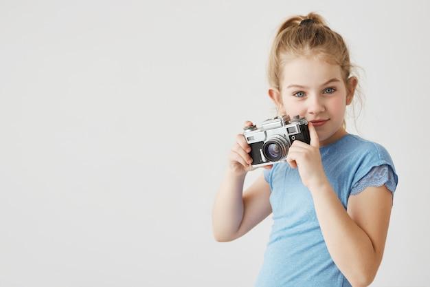 Portret van zelfverzekerde jonge dame met blauwe ogen en blond haar poseren met haar fotocamera laten zien dat ze fotograaf wil worden. kopieer ruimte
