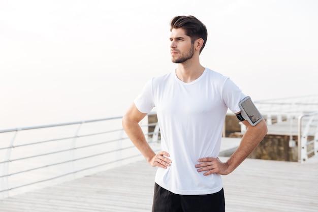 Portret van zelfverzekerde jonge sportman met mobiele telefoon in armband