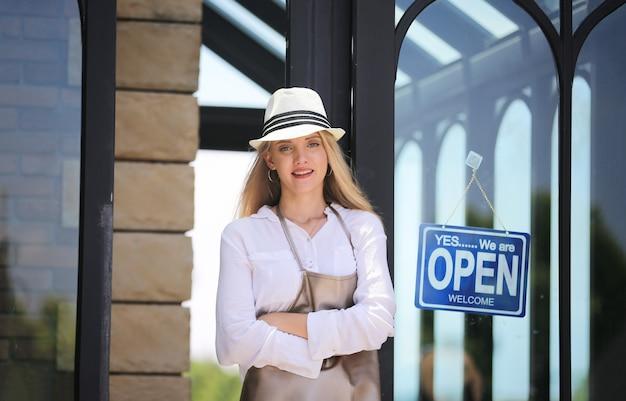 Portret van zelfverzekerde jonge vrouwelijke winkel, eigenaar van een coffeeshop voor kleine bedrijven