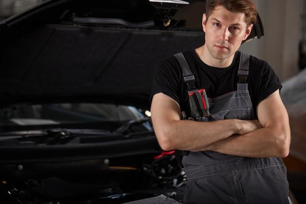 Portret van zelfverzekerde kaukasische monteur in uniform poseren bij camera in autoservice