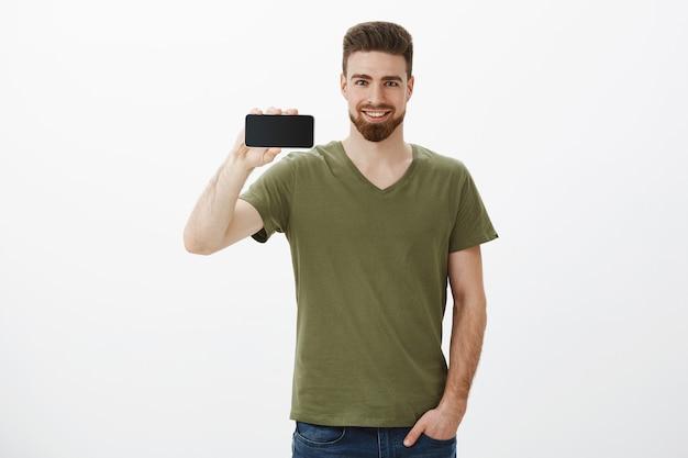 Portret van zelfverzekerde knappe bebaarde mannelijke collega smartphone horizontaal houden en glimlachend opgetogen