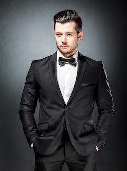 Portret van zelfverzekerde knappe man in zwart pak met bowtie