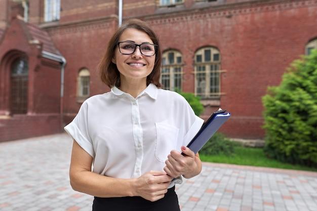Portret van zelfverzekerde lachende zakenvrouw, vrouwelijke leraar, counselor met klembord papieren documenten. positieve lachende vrouw, schoolgebouw, kantoorgebouw achtergrond