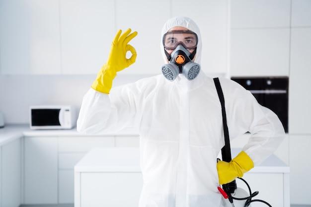 Portret van zelfverzekerde man toont ok teken latex handschoenen bevelen uitstekende kwaliteit aan