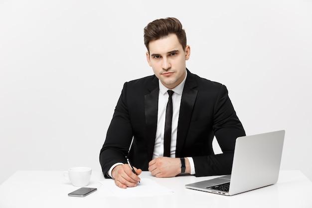 Portret van zelfverzekerde manager die aan het bureau zit en naar camera kijkt portret van zakenman aan het werk...