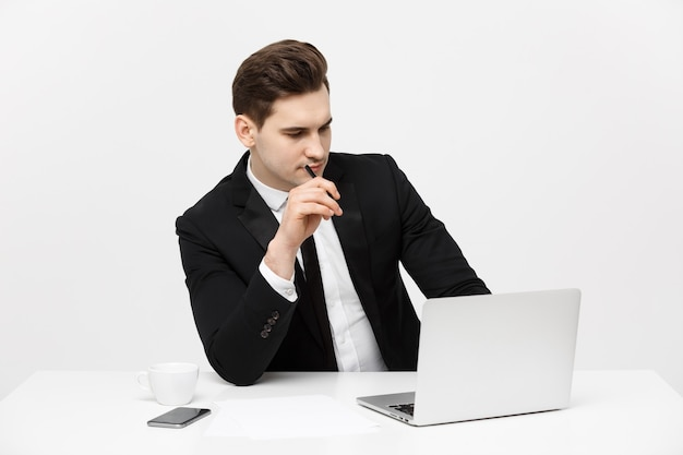 Portret van zelfverzekerde manager zit aan de balie. portret van zakenman aan het werk op de computer. succesvolle formele man in zijn nieuwe moderne kantoor.